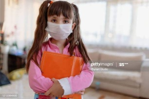 little girl wearing face mask at home